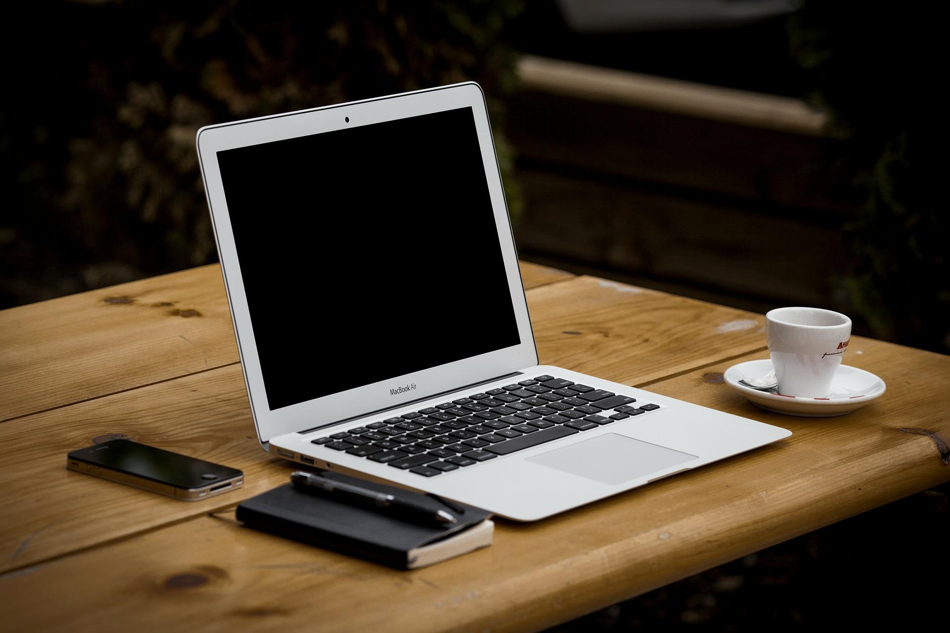 Laptop zum Bloggen auf einem Tisch nebst Kaffeetasse, Smartphone und Block mit Stift