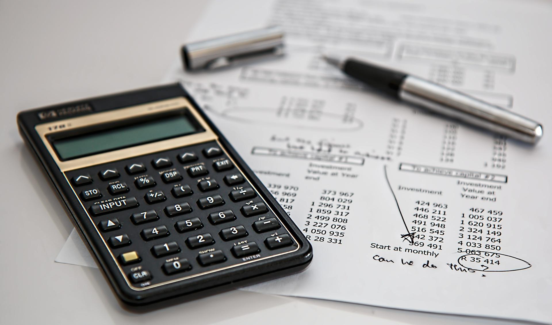 Taschenrechner, ein Stift und eine Liste mit Zahlen liegt auf einem Tisch.