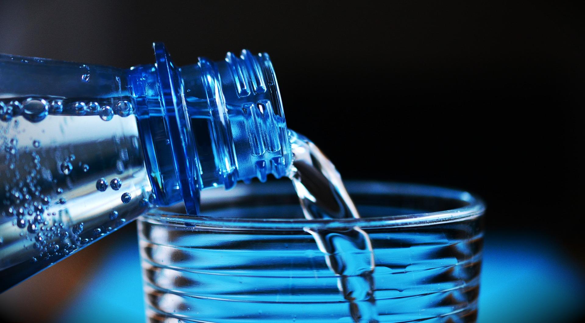 Wasser aus einer PET-Flasche wird in ein Glas gegossen.